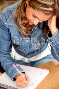 Image of girl writing on a note pad